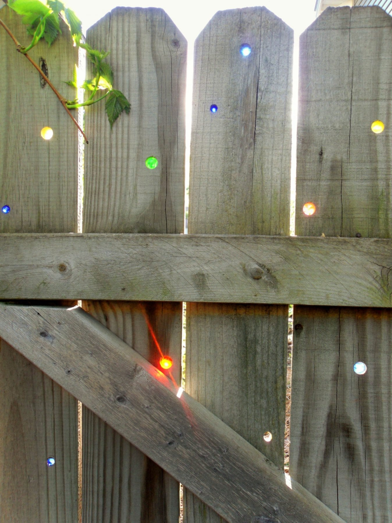Garden art on the cheap DIY: Glass marbles in your fence